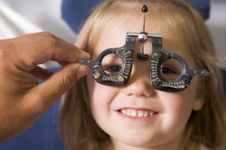 image-of-a-young-girl-with-eye-testing-equipment-held-in-front-of-face-450x300