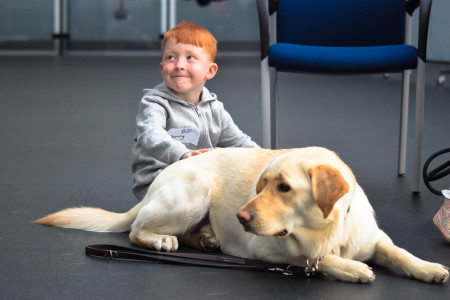 sonny sat on the floor stroking a guide dog at the Guide Dog centre in atherton