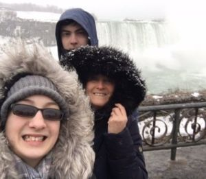Samantha and family in front of a large waterfall
