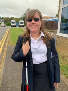 Emma in her school uniform with her cane