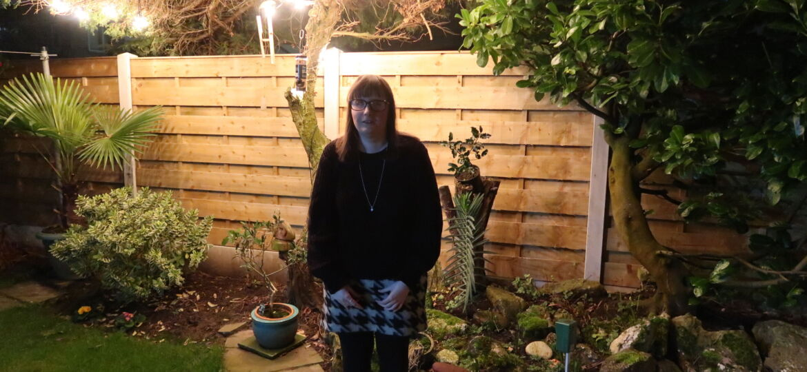 Holly stood in a garden with a wooden fence behind and lights in a tree, there is a garden rockery at the side, wearing a black jumper, a black and white skirt with black leggings and black boots