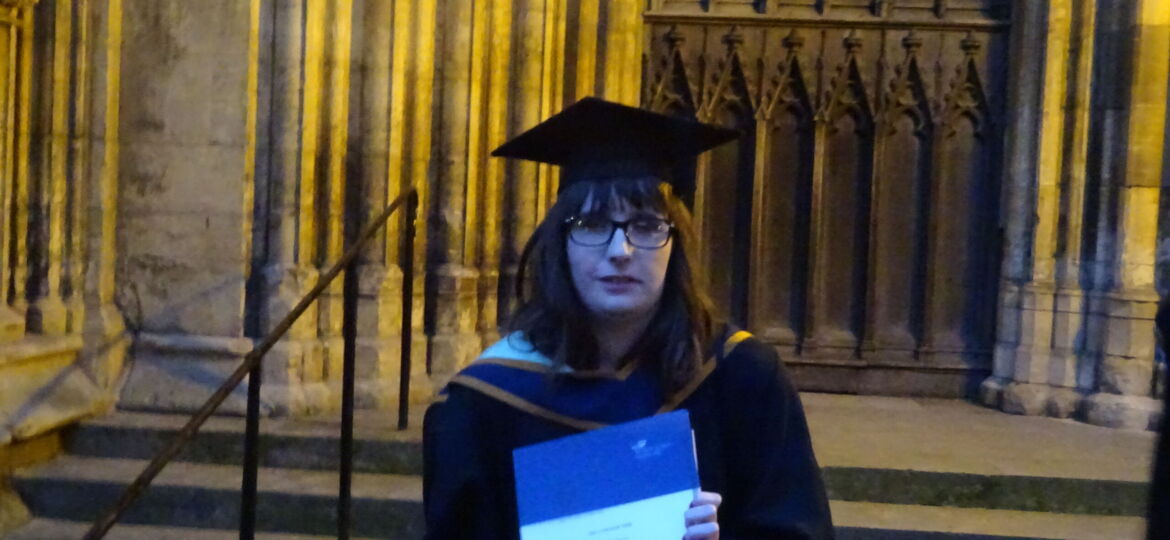 Holly stood outside York Minster holding her graduation certificate she is wearing a black gown and black mortarboard hat