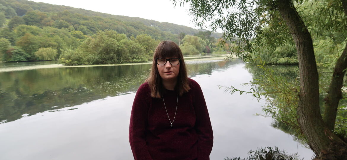 Holly stood underneath a willow tree, she is wearing a burgundy jumper, black leggings and silver necklace. A lake and trees can be seen in the background