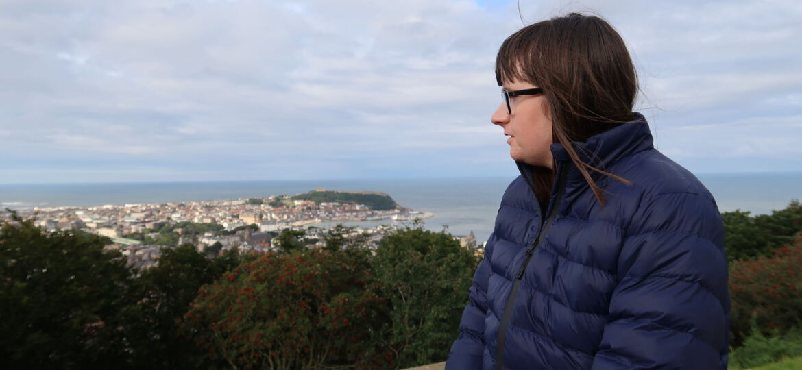 Holly leant against a stone wall looking to the side, she is wearing a blue padded jacket. A mass of trees and a bay can be seen in the distance